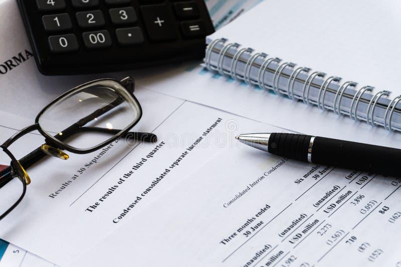 Relatório financeiro da declaração de rendimentos com pena e vidro imagem de stock