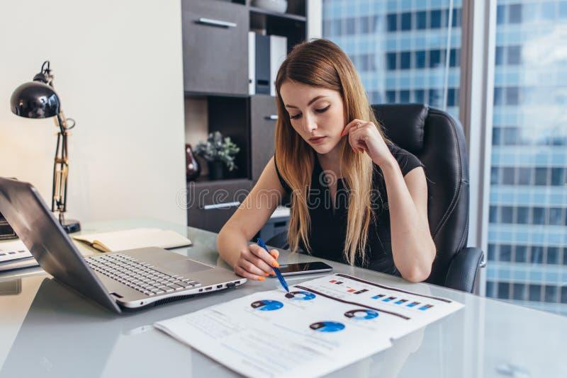 Relatório financeiro do readind fêmea da mulher de negócios que analisa as estatísticas que apontam na carta de torta que trabalh imagens de stock
