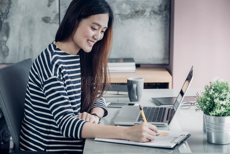 Relatório ocasional asiático novo na mesa de escritório, w da escrita da mulher de negócios fotos de stock royalty free