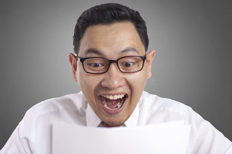 Relatório surpreendido de sorriso feliz de Reading Positive Financial do homem de negócios fotos de stock