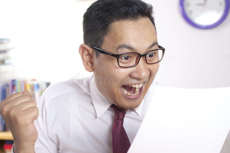 Relatório surpreendido de sorriso feliz de Reading Positive Financial do homem de negócios imagens de stock royalty free