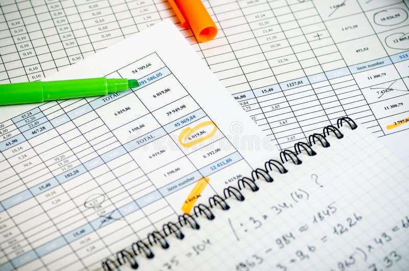 Relatórios explicando nas tabelas, em um caderno de papel com cálculos de lucro e em highlighteres fotos de stock