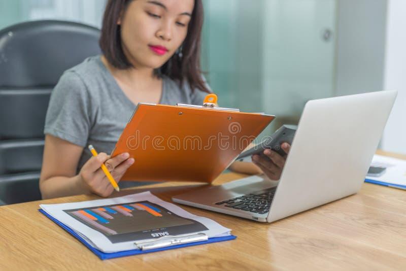 Relatórios financeiros de leitura da mulher de negócios asiática nova imagens de stock royalty free
