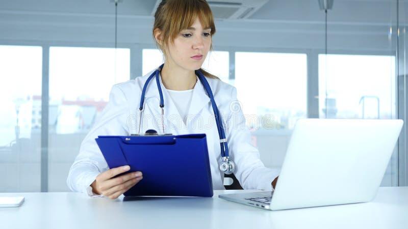 Relatórios médicos de leitura do doutor fêmea novo e trabalho no portátil fotos de stock royalty free