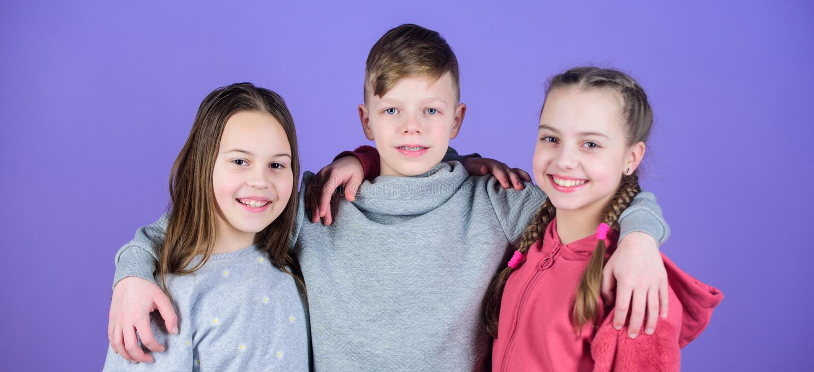 Relations and friendship. Happy to have such good friends. Teens friends. Girl and boy true friendship. Children smiling. Faces on violet background. Friends royalty free stock images