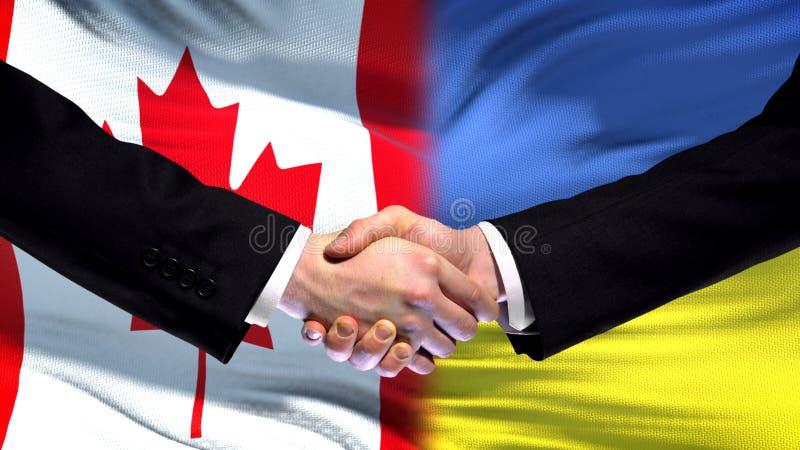 Relations internationales d'amitié de poignée de main de Canada et de l'Ukraine, fond de drapeau photos stock