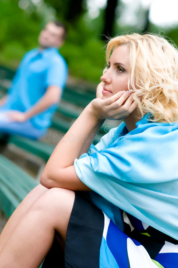 Relationship. Young woman and man sitting on a bench in park, selective focus stock photo