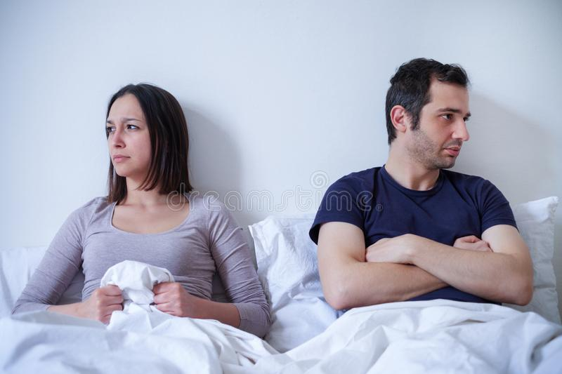 Sad couple and relationship difficulties in bed. Relationship bed problem and couple ling in bed stock photography