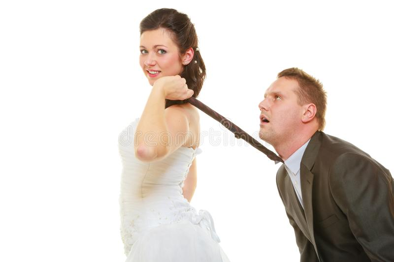 Dominant bride wearing wedding dress pulling groom tie stock photo