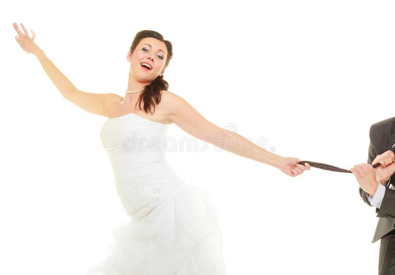 Dominant bride wearing wedding dress pulling groom tie stock photography