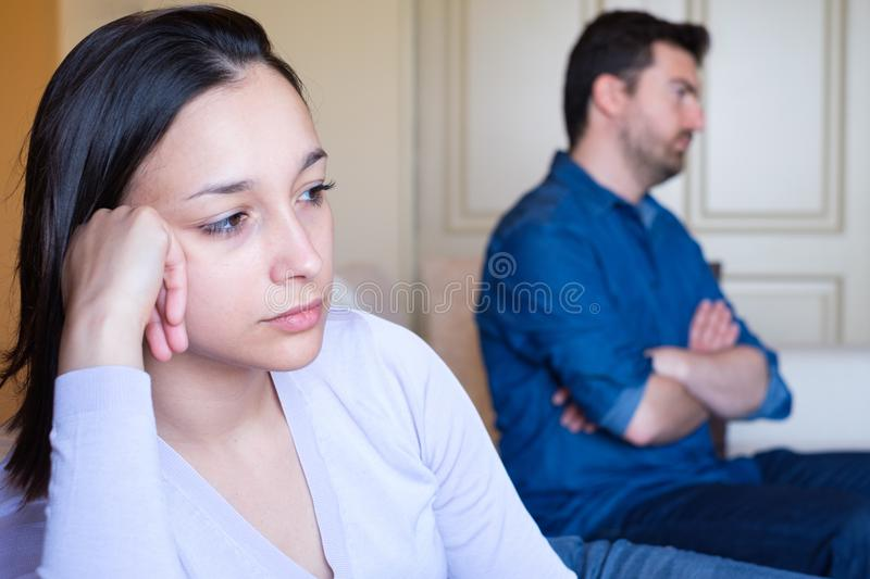 Relationship difficulties. Bored young couple sitting on the sofa stock image
