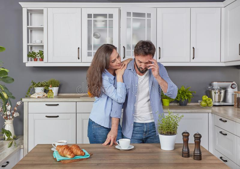 Relationship difficulties concept. Upset young couple in the kitchen royalty free stock photos
