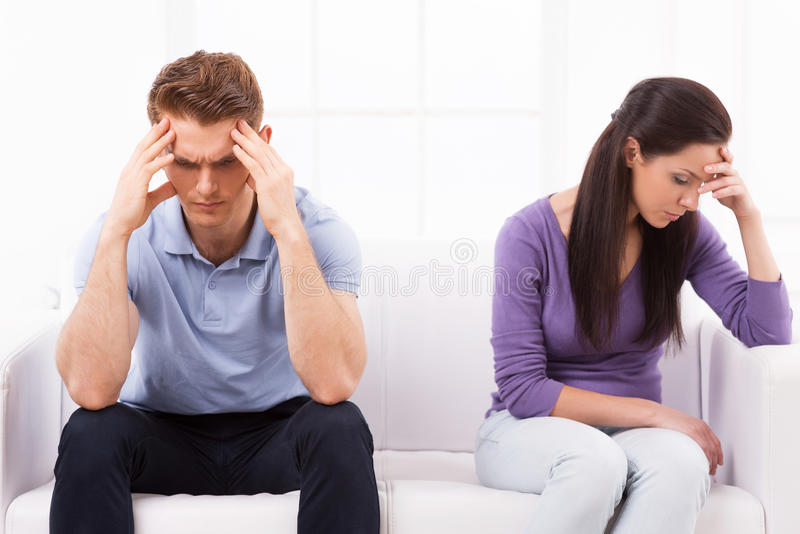 Relationship difficulties. Depressed young men and women sitting close to each other on the couch and holding head in hands royalty free stock photography