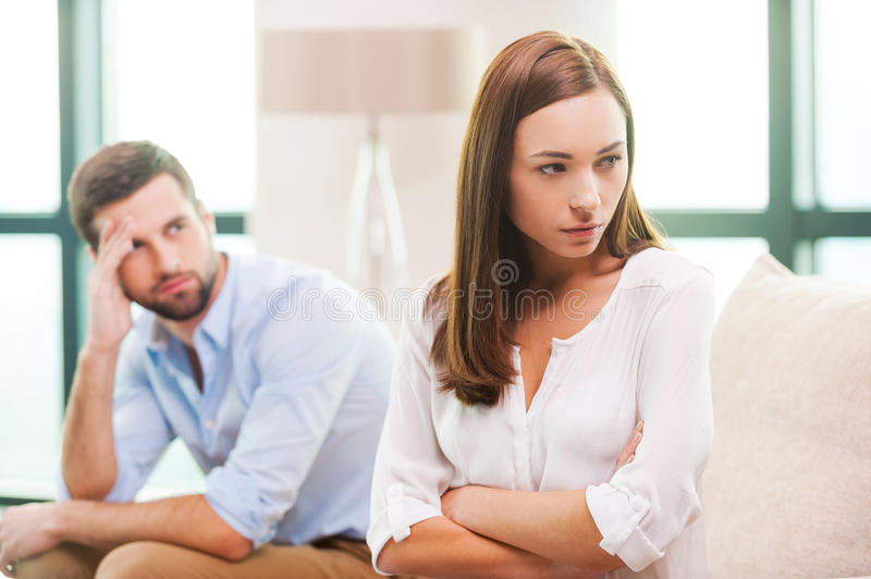 Relationship difficulties. Depressed young women keeping arms crossed and looking away while men sitting behind her on the couch royalty free stock images
