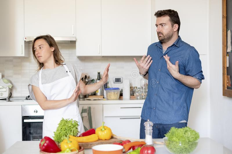 Relationship difficulties during the food preparation. Couple arguing about cooking at home in the kitchen royalty free stock photo