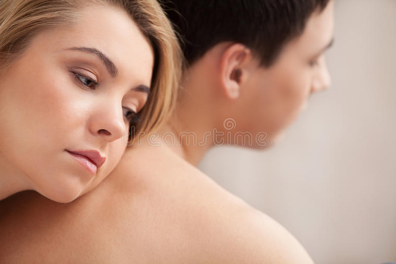 Relationship difficulties. Young depressed women leaning at her boyfriend back and looking away royalty free stock photo