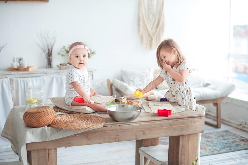 Relationship in the family with small children. Two sisters are cooking in the bright kitchen. Small children help to cook, the co royalty free stock photo
