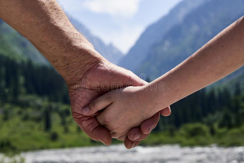 Relationship between generations. Closeup photo of a child`s hand of his elderly grandfather royalty free stock images