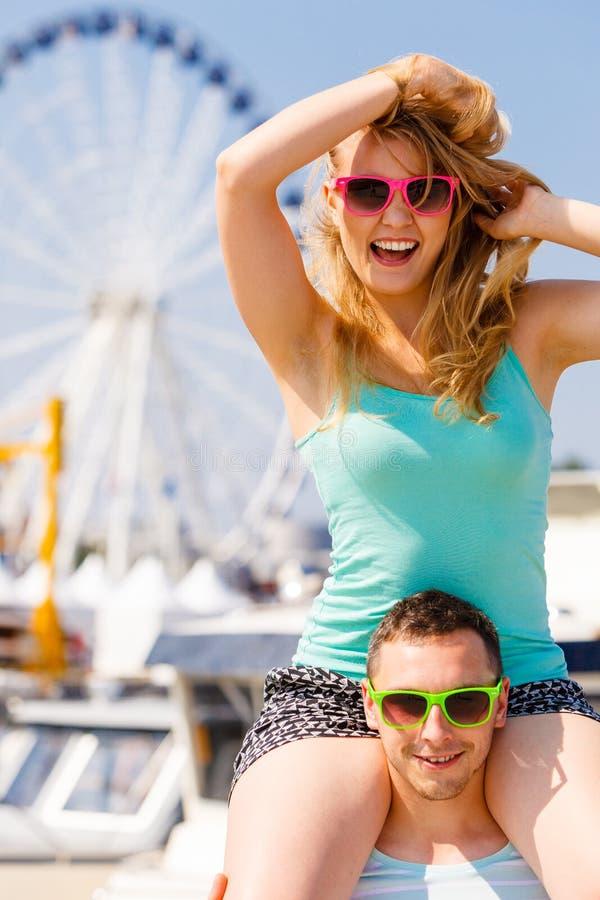 Man giving girlfriend piggyback ride on marina royalty free stock image