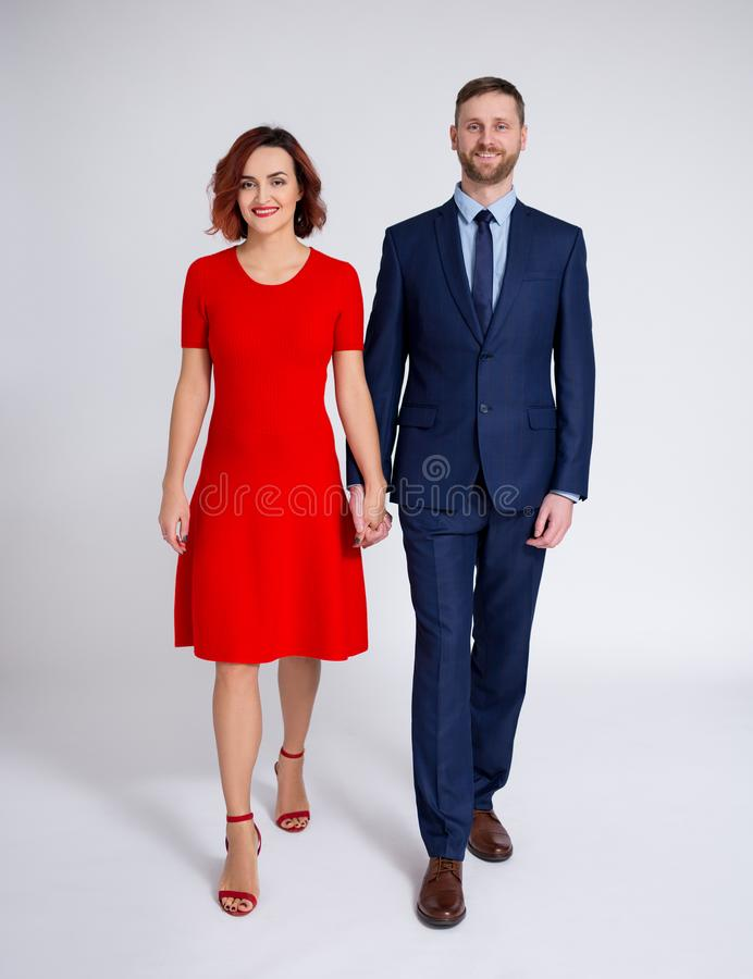 Relationship and love concept - front view of couple in love holding hands and walking over white royalty free stock image