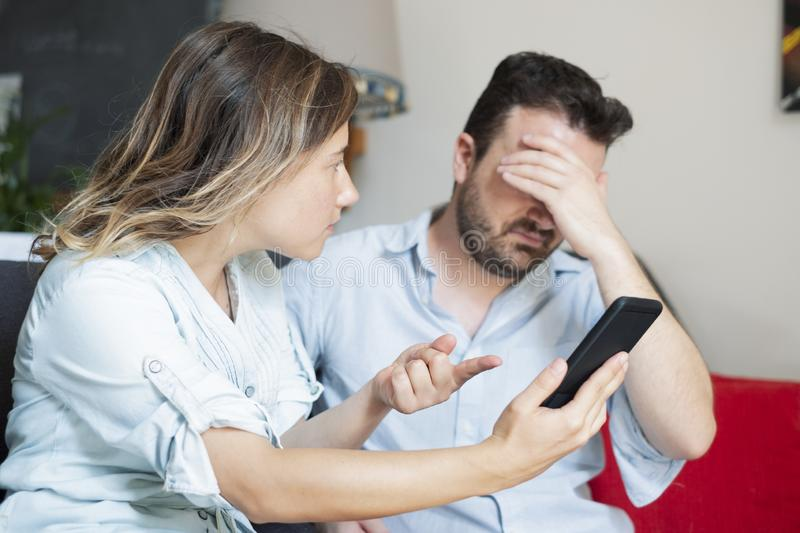 Relationship problem because of jealousy and infidelity. Boyfriend caught by girlfriend while cheating with mobile phone royalty free stock image