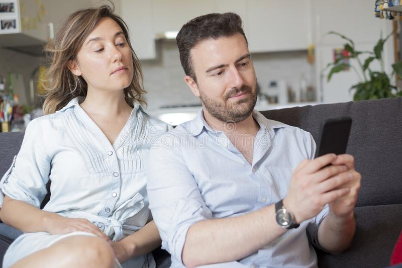 Relationship problem because of jealousy and infidelity. Boyfriend caught by girlfriend while cheating with mobile phone royalty free stock photography