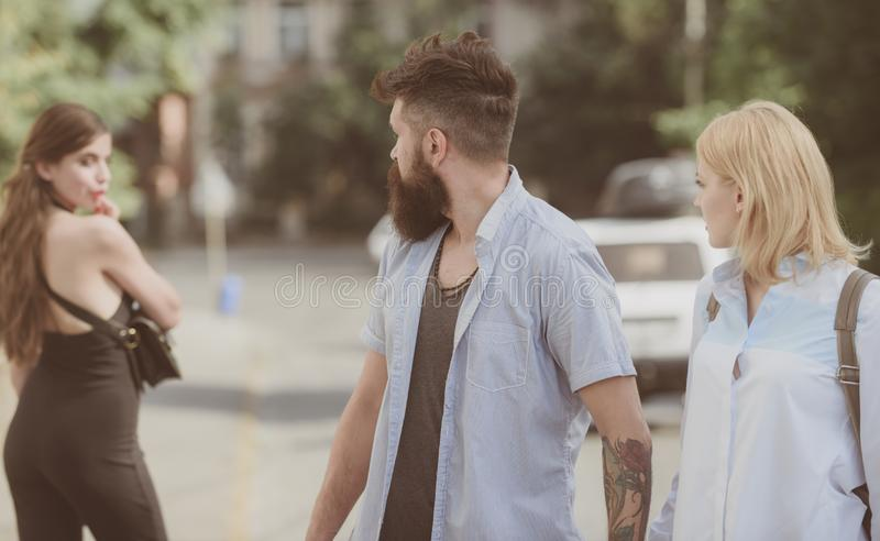 Relationship problem. Man cheating his wife or girlfriend. Bearded man looking at other girl. Hipster choosing between royalty free stock image