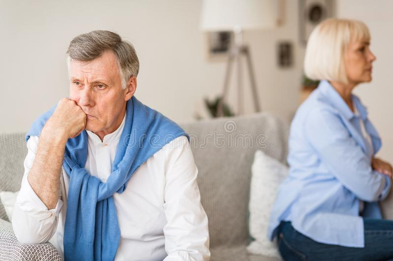 Relationship problems. Senior couple after argument sitting on sofa stock photos