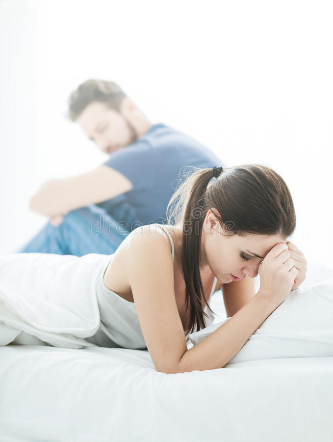 Relationship problems. Young couple in the bedroom having relationship difficulties and arguing, the women is crying stock image