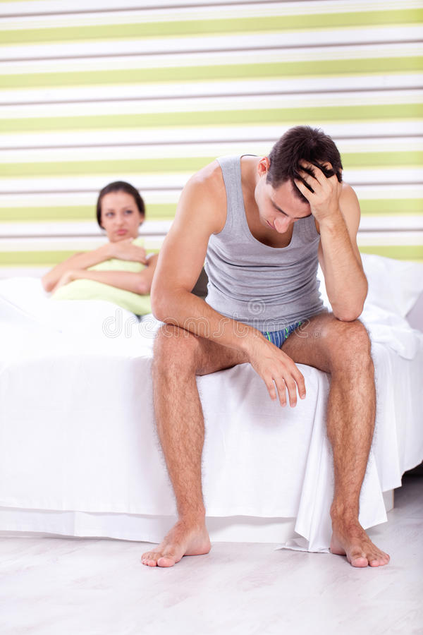 Relationship trouble. Upset men sitting on bed with his wife in background, relationship trouble stock photography