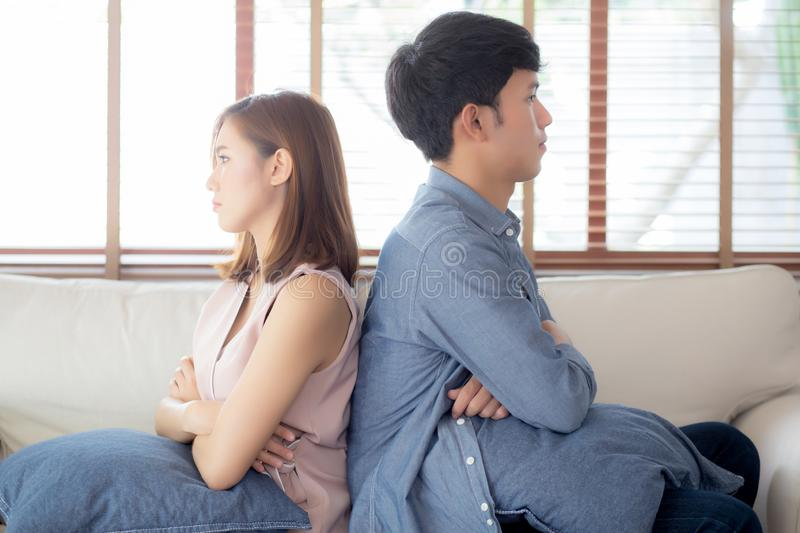 Relationship of young asian couple having problem on sofa in the living room at home, family having conflict argument royalty free stock photography