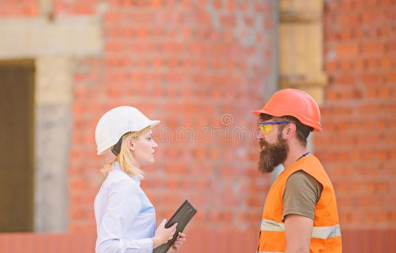 Relationships construction client and participant building industry. Discuss progress plan. Construction industry. Concept. Woman engineer and bearded brutal stock photo