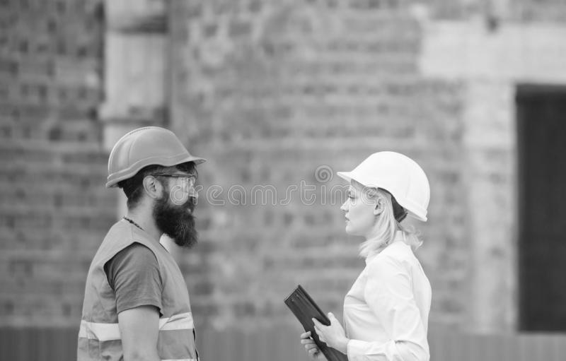 Relationships construction client and participant building industry. Discuss progress plan. Construction industry. Concept. Woman engineer and bearded brutal stock image