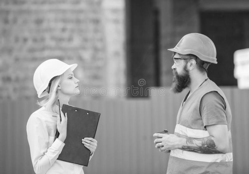Relationships construction client and participant building industry. Discuss progress plan. Woman engineer and bearded. Brutal builder discuss construction stock image