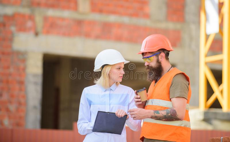 Relationships between construction clients and participant building industry. Discuss progress plan. Woman engineer and. Builder communicate construction site royalty free stock image