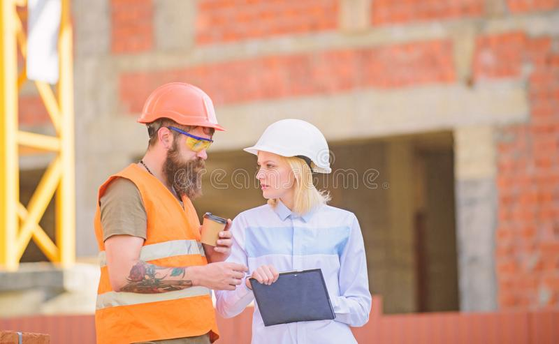 Relationships between construction clients and participant building industry. Discuss progress plan. Woman engineer and. Builder communicate construction site royalty free stock photo