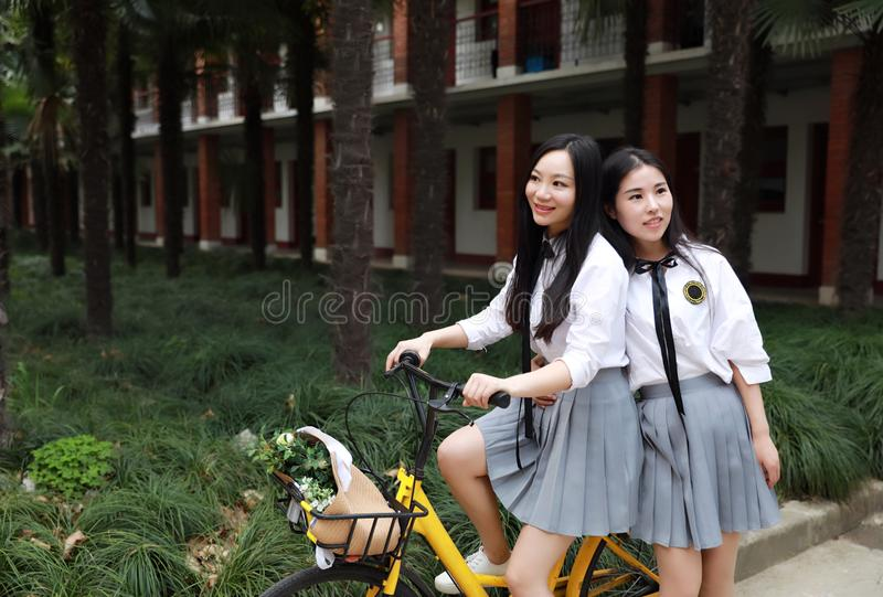 Relax Asian Chinese pretty girls wear student suit in school enjoy free time ride bike in nature spring garden royalty free stock image