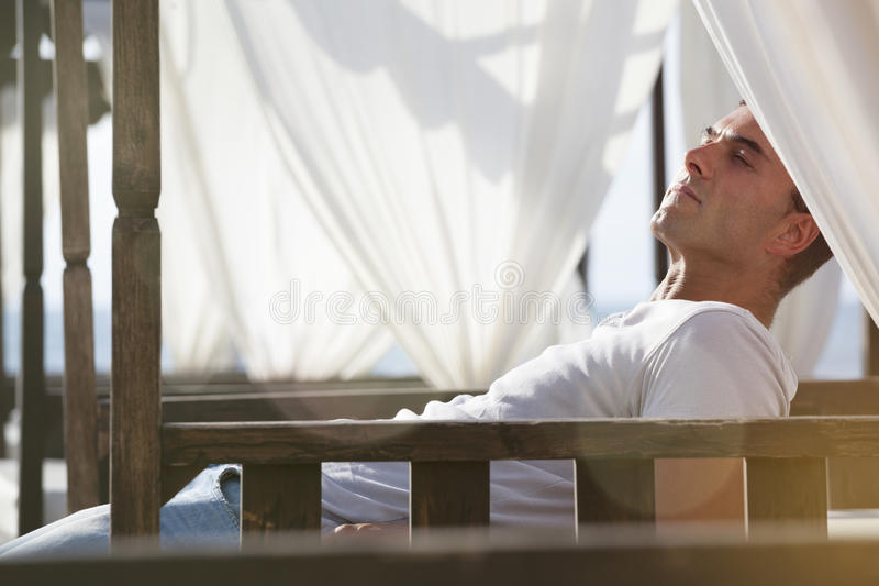 Relax serenity at the beach. Man lying on canopy wooden beds white curtains. A man relaxed on the outdoor bed. Closed eyes and contemplation. Holiday concept royalty free stock photo