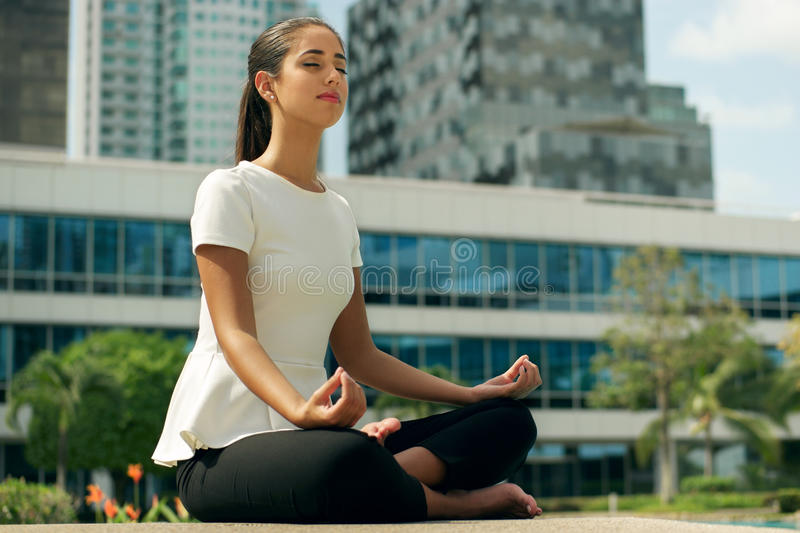 Relax Business Woman Yoga Lotus Position Outside Office Building. Young stressed hispanic business woman doing yoga outside office building, sitting in lotus royalty free stock photo