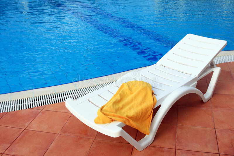 Relax chair near the pool with towel royalty free stock photography