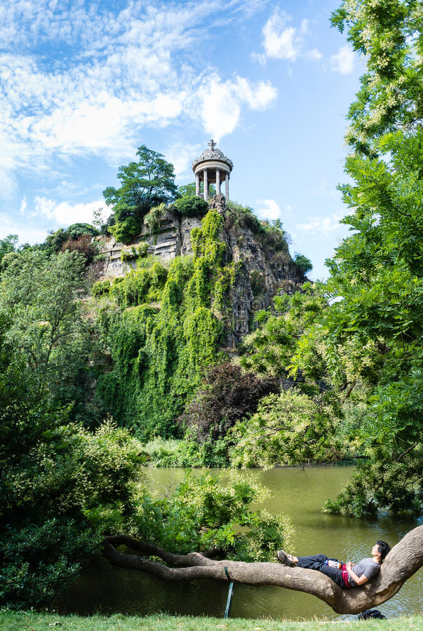 Relax. Chilling in the warm sunlight, in a green and beautiful parc in Paris - Buttes Chaumont. After a long jogging session, time to recover surrounded by a stock images
