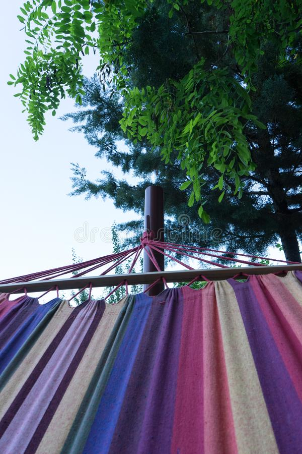 Relax on Colorful hammock on the tree in the forest. Camping night with fabric with rainbow colors. Home relaxing in the garden stock image