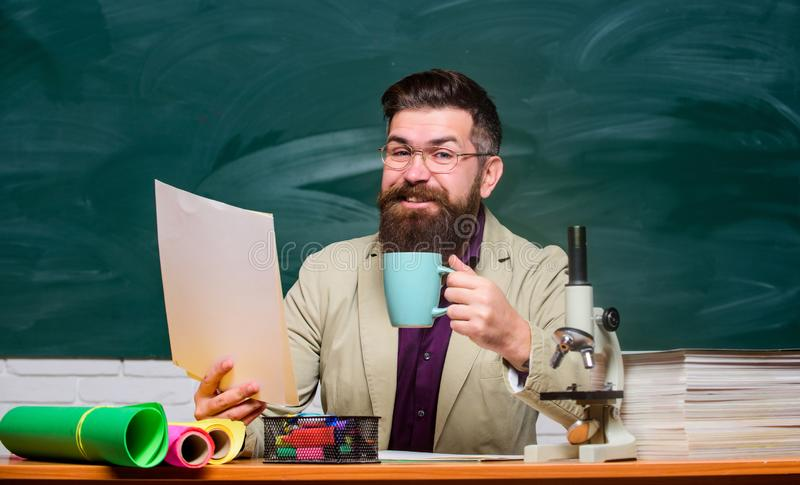 Relax concept. College and high school teacher. Reading essay. Handsome teacher relaxing. Teacher bearded man drinking royalty free stock image