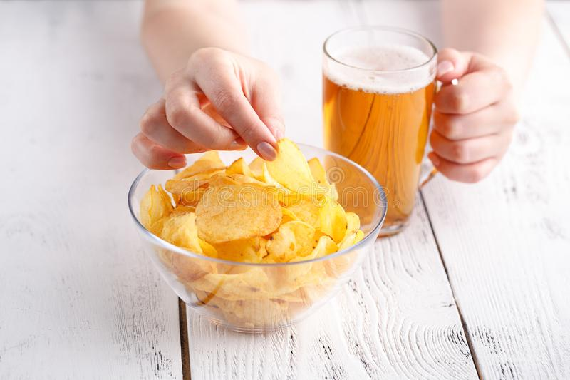 Relax dinner with Beer and potato Chips, female at home royalty free stock image