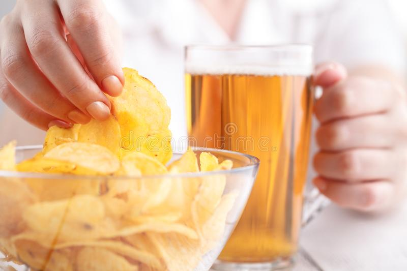 Relax dinner with Beer and potato Chips, female at home stock photos