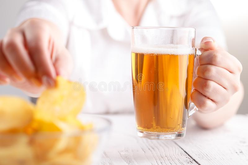 Relax dinner with Beer and potato Chips, female at home stock photography