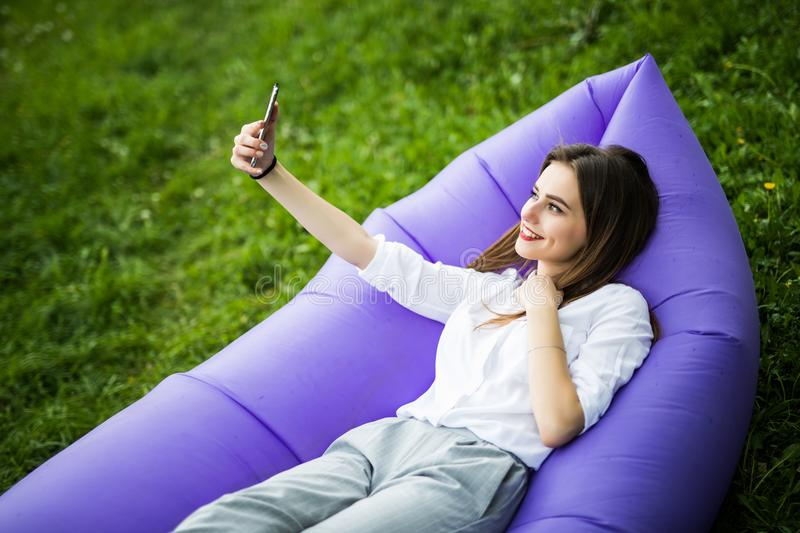 Relax on fresh air. Pretty young woman lying on inflatable sofa lamzac use mobile phone while resting on grass in park on the sun. Pretty young woman lying on royalty free stock photography