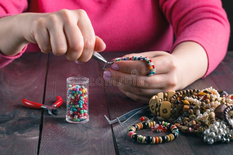 Relax hobby. Female make craft beads stock image