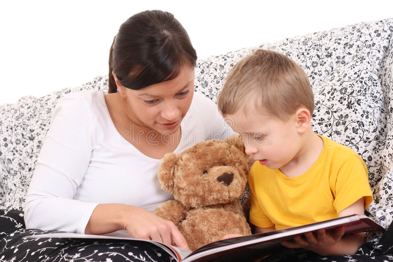 Relax with mother. Mother and son in bed with book - relax royalty free stock photo