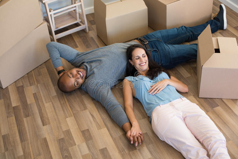 Relax in new home. Happy multiethnic couple lying on floor after moving house. Top view of young women lying on stomach of black men with cardboard boxes around stock photo